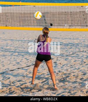 Une adolescente qui est en train de mettre la balle au cours d'un match de volley-ball de plage avec l'océan en arrière-plan. Banque D'Images