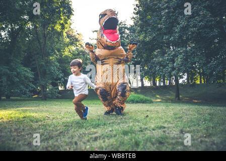 Père et fils à jouer au parc, avec un costume de dinosaure, s'amusant avec la famille piscine