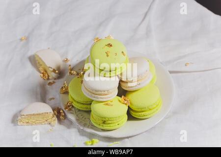 Beaucoup de macarons colorés sur la plaque de céramique blanche sur la table Banque D'Images