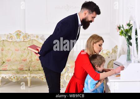 Les parents bénéficiant de parent, l'enseignement enfant à écrire. Concept d'enseignement à domicile. Père peeking, tandis que mère, les fils d'âge préscolaire à dessiner ou écrire, l Banque D'Images