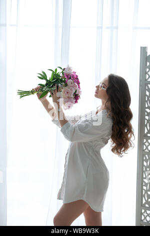 Belle jeune fille enceinte avec un bouquet de fleurs à la fenêtre Banque D'Images
