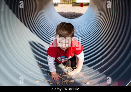 Un petit garçon lentement à une aire de tunnel, explorer et s'amuser