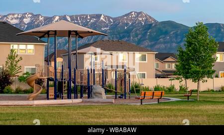 Châssis Panorama Aire de jeux sur un parc en face de chez eux avec des clôtures en bois blanc Banque D'Images