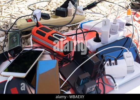 De nombreuses prises électriques connectés à une prise multiple ou d'extension du bloc. Chargeurs de mur branché à un gang. Les smartphones, gadgets de charge électronique et Banque D'Images