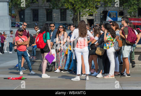 Groupe de touristes sur une visite guidée à Trafalgar Square, Charing Cross, City of Westminster, Londres, Angleterre, Royaume-Uni. Guide touristique à Londres. Banque D'Images
