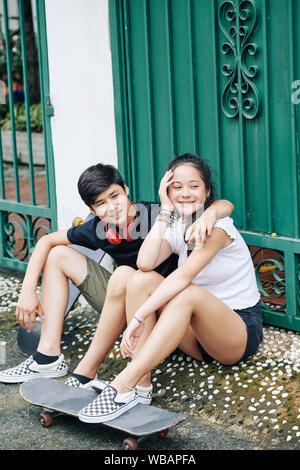Frère et sœur jumeaux souriant assis dans la rue avec leurs planches à roulettes et à l'écart Banque D'Images