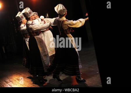 Folk Dancers en estonien les vêtements nationaux produisent sur scène d'intérieur