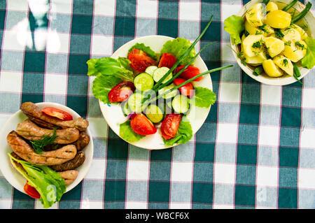 Sur la table des plats - légumes, pommes de terre, saucisses bavaroises. L'arrière-plan. Banque D'Images