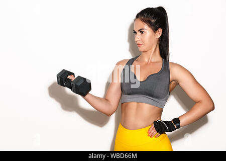 Image of young woman fitness isolated over white wall background holding dumbbell. Banque D'Images