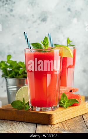 La sauce au melon d'eau avec citron vert et menthe, une boisson rafraîchissante d'été dans de grands verres sur fond bleu clair. Smoothie doux et froid