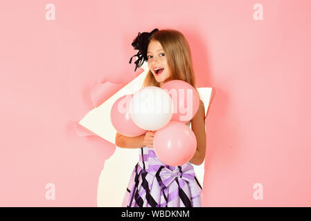 Petite fille avec des ballons sur fond rose. Banque D'Images