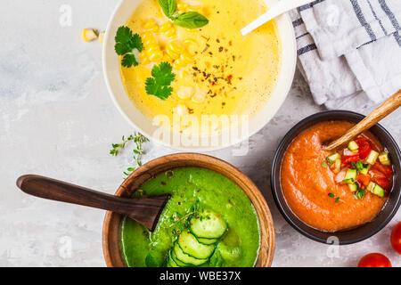 Trois différentes soupes crème de légumes dans des bols sur un fond gris. Le maïs, le concombre et le gazpacho de soupes. Banque D'Images