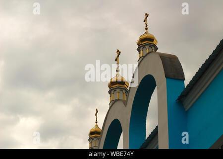 Dômes dorés avec croix sur le bleu-blanc arcades de l'Eglise orthodoxe contre le ciel bleu Banque D'Images