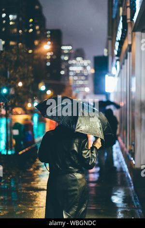 Vue arrière de l'homme marchant sur la rue la nuit humide Banque D'Images