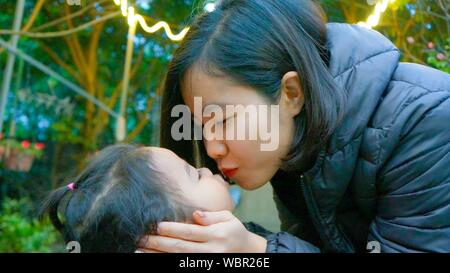 Close-up of mother and daughter Kissing Outdoors Banque D'Images