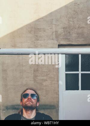 Jeune homme à la maison jusqu'en position debout contre Banque D'Images