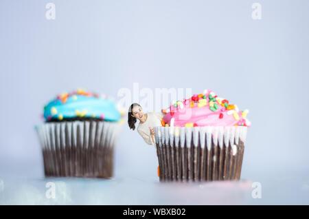 Image Composite numérique de jeune femme se cachant derrière Cupcakes Against White Background