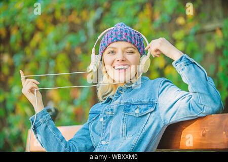 L'apprentissage en ligne. L'écoute de la musique en ligne en parc. livre audio en ligne. Le style et la musique. Vous pourrez vous détendre dans le parc. hipster girl avec un lecteur mp3. La technologie moderne au lieu de lecture. hipster femme dans le casque. Banque D'Images