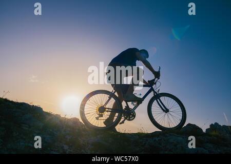 Silhouette d'un homme fit du vélo de montagne équitation son vélo en montée sur des terrains difficiles sur un coucher de soleil. Banque D'Images