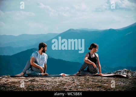 Jeune couple fort et flexible d'entraînement yoga. Homme et femme sur la pratique de la montagne en matin yoga paire Banque D'Images