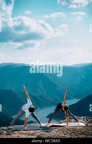 Jeune couple fort et flexible d'entraînement yoga. Homme et femme sur la pratique de la montagne en matin yoga paire
