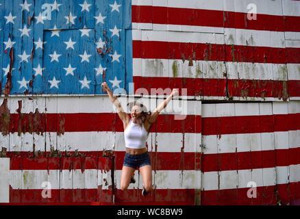 Excitée femme sautant contre drapeau américain peint sur mur Banque D'Images
