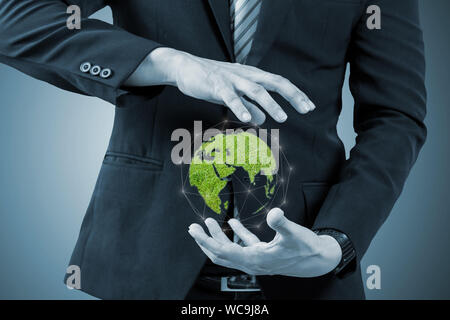 Digital Composite Midsection Of Businessman Holding Globe Vert Banque D'Images