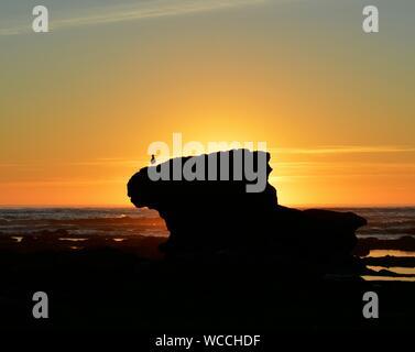 Rocher sur la plage Silhouette contre le ciel au coucher du soleil Banque D'Images