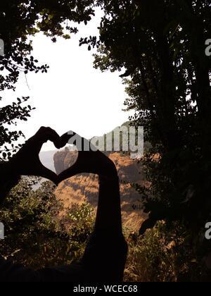 Close-up of Cropped Silhouette mains Faire forme de coeur contre des arbres Banque D'Images