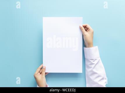 Close up hands holding empty white blank lettre format de papier A4 pour flyer ou invitation maquette isolé sur un fond bleu. Banque D'Images