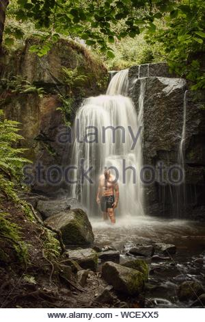 Man Standing Under Waterfall In Forest Banque D'Images