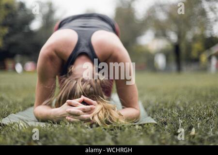 Woman Practicing Wavecrest On Grassy Field Banque D'Images