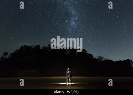 Homme debout sur le terrain contre un ciel étoilé de nuit Banque D'Images