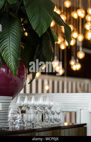 Nettoyer les verres vides sur la table à côté d'une pile d'assiettes blanches avec une nappe blanche dans un restaurant à l'intérieur. Buffet de la fête. Guirlandes Banque D'Images