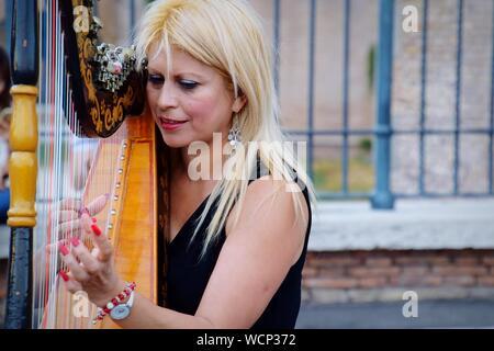 Portrait de femme jouant de la Harpe On City Street Banque D'Images
