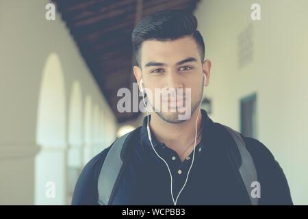 Portrait de jeune homme à l'écoute de la musique sur Earphones Banque D'Images