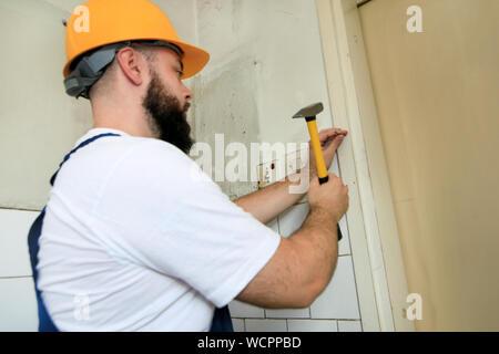 Travailleur de la construction et l'homme à travailler sur des travaux de rénovation. Builder avec marteau frappe jaune et des ongles un clou dans le mur en bois de porte de la cuisine.