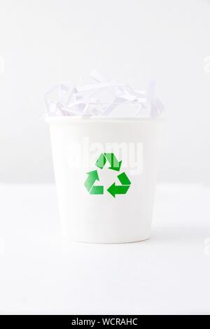 Signe de recyclage sur gobelet jetable avec des papiers sur fond blanc Banque D'Images
