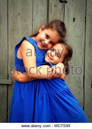 Portrait Of Smiling Siblings Embracing debout contre le mur en bois Banque D'Images