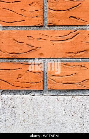 Mur de brique rouge sur fondation en béton. Close-up arrière-plan. Un motif de branches sculptés sur la surface. L'espace de copie dans la partie centrale de l'image. Construction Banque D'Images