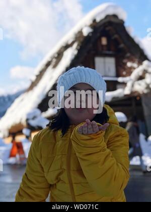 Portrait Of cute girl Blowing Kiss en se tenant debout dans la neige Banque D'Images