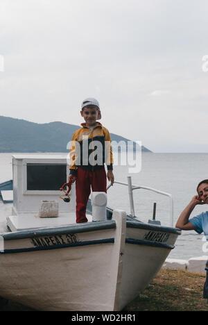 Portrait de garçon debout sur le bateau au port contre les montagnes et le ciel Banque D'Images