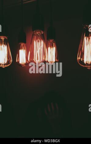 Close-up of Illuminated Ampoules suspendues dans Darkroom Banque D'Images