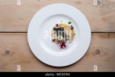 Une tête de petits calzones avec feuilles de légumes sur le dessus dans un cercle blanc sur la plaque d'une surface en bois Banque D'Images