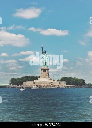 Low Angle View Of Statue de la liberté en face de mer contre Ciel Bleu Banque D'Images
