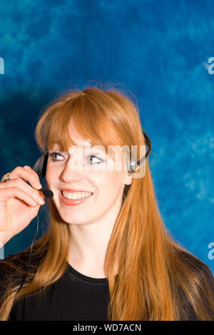 Close-up of Young Woman Wearing Headphones Par Blue Wall Banque D'Images