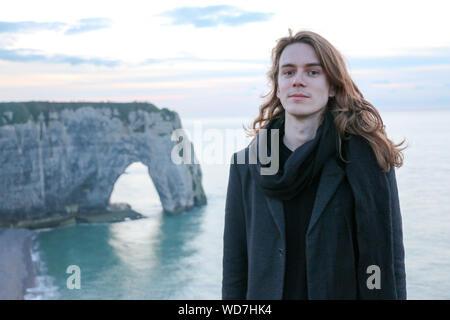 Portrait d'Homme debout sur la falaise contre la mer au coucher du soleil Banque D'Images