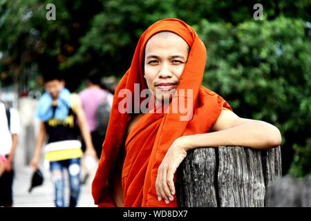 Portrait Of Smiling Monk Leaning On Wooden Post Banque D'Images