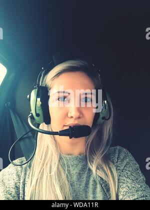 Portrait de femme portant des écouteurs en hélicoptère Banque D'Images