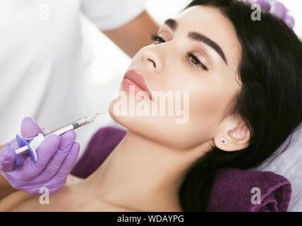 Traitement visage cosmétique. Belle femme d'âge moyen se font face à l'injection, l'effet de levage, la beauté les injections pour l'ascenseur de visage et contour visage serrer